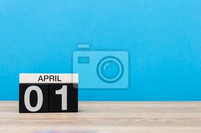 Fototapeta 1 kwietnia. Dzień 1 miesiąca, kalendarz na drewnianym stole i niebieskim tle. Wiosna, puste miejsce na tekst