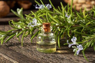 Fototapeta A bottle of rosemary essential oil with fresh rosemary