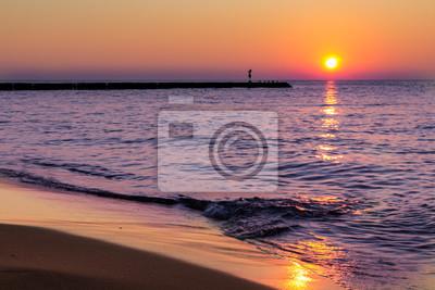 Fototapeta A spokój, spokojny zachód słońca nad morzem i łagodne fale rozpryskiwania na plaży.