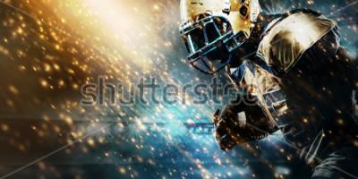 Fototapeta American football sportsman player on stadium running in action. Sport wallpaper with copyspace.