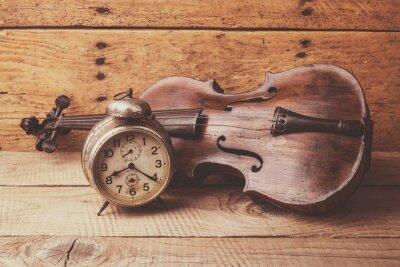 Fototapeta Antyczny zegar i stare skrzypce na drewnianym stole rocznika
