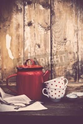 Fototapeta Archiwalne wystrój kuchni, szkła emaliowane kawy i filiżanki z polka kropki na starym tle drewniane deski z miejsca kopiowania. Rustykalny wystrój domu.
