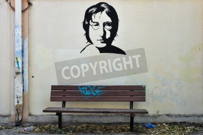 Fototapeta ATHENS, GREECE - AUGUST 30, 2014: Famous musician John Lennon from The Beatles portrait stencil graffiti on textured wall and wooden bench.