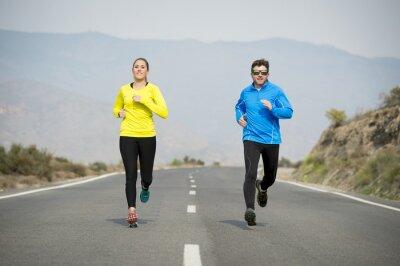 Fototapeta atrakcyjny sportowy para mężczyzna i kobieta pracuje razem na asfaltu drogowego krajobrazu górskiego