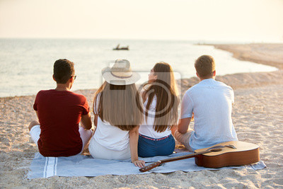 Fototapeta Back view of group of friends sitting together on towel on white sand beach during their vacation and enjoying a sunset above the sea. Men and women relax on the shore with guitar. Tranquil scene.