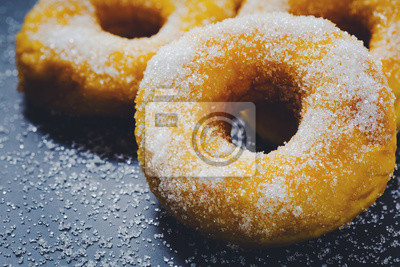 Fototapeta Bakery sweet donuts sprinkled with sugar powder on white plate on black table background