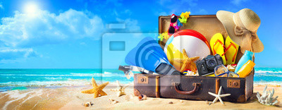 Fototapeta Beach accessories in suitcase on sand. Family holidays concept