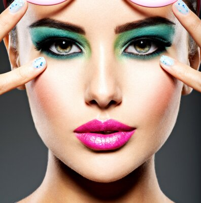 Fototapeta Beautiful Face of a woman with green vivid make-up of eyes
