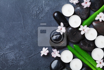 Beautiful spa background with massage pebble, green leaves, flowers and candles on black stone table top view. Aromatherapy, beauty, relaxation and zen like concept.