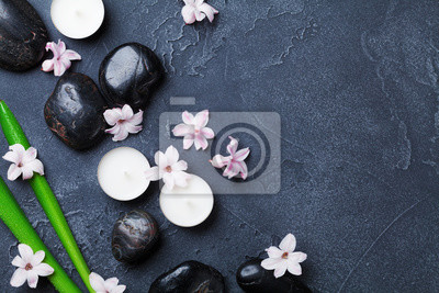 Beautiful spa background with massage pebble, green leaves, flowers and candles on black stone table top view. Aromatherapy, relaxation and zen like concept.