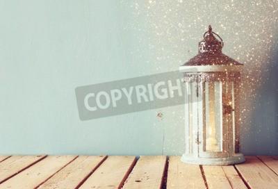 Fototapeta Białe drewniane rocznika Latarnia z Świecę i gałęzie drzewa na drewnianym stole. retro filtrowany obraz z brokatem nakładki