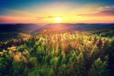 Fototapeta Bird's-eye view of a scenic sunset over the   forest hills, with toned dramatic colors