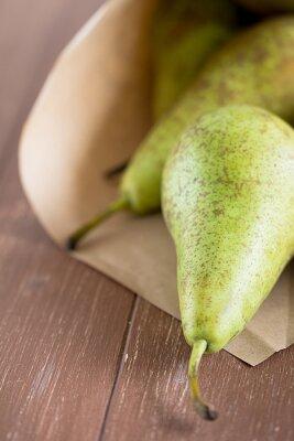 Fototapeta Birnen spadł aus einer Obsttüte auf ein Holzbrett