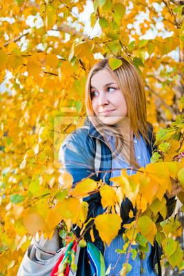 Fototapeta bliska, Portret kobiety jesienią z żółtych liści