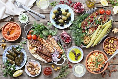 Fototapeta Bliskowschodni, arabski lub śródziemnomorski stół obiadowy z grillowanym kebabem jagnięcym, szaszłyki z kurczaka z pieczonymi warzywami i różnorodne przekąski na drewnianym stole zewnętrznym. Widok z