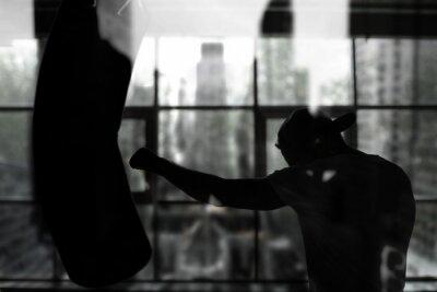 Fototapeta Bokser uderza w worek treningowy przed oknem, treningu