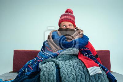 Fototapeta Brodaty chory człowiek z kominkiem siedzi na kanapie w domu lub studio pokryte dzianiny ciepłe ubrania. Choroba, grypa, koncepcja bólu. Relaks w domu. Koncepcje opieki zdrowotnej.