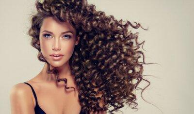Fototapeta Brunetka dziewczyna z długimi i błyszczącymi kręcone włosy. Piękny model z falistą fryzurą.