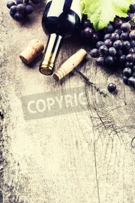 Fototapeta Butelka wina, ciemne winogron i korki na starym drewnianym tle