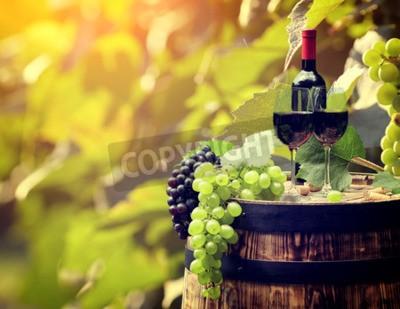 Fototapeta Butelkę czerwonego wina i kieliszek do wina na wodden beczki.
