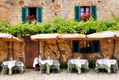 Fototapeta Cafe stoły i krzesła na zewnątrz budynku z kamienia w Toskanii
