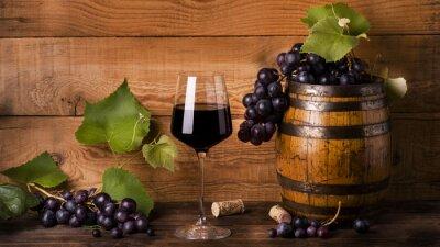 Fototapeta calice di vino rosso con uva e botte