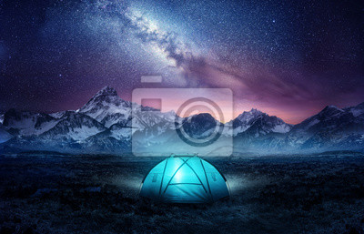 Fototapeta Camping in the mountains under the stars. A tent pitched up and glowing under the milky way. Photo composite.
