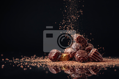 Fototapeta Chocolate candies on a black background sprinkled with chocolate chips.
