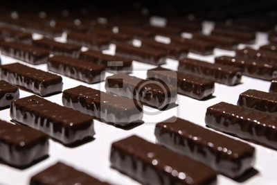 Fototapeta chocolate candies on the conveyor of a confectionery factory close-up