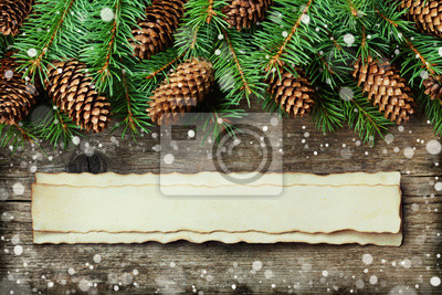Christmas background of fir tree and conifer cone on old vintage wooden board, fantastic snow effect and aged paper with copy space for text, top view