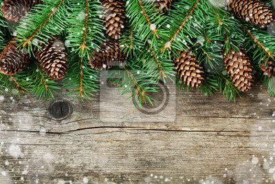 Christmas decoration of fir tree and conifer cone on textured wood background, magic snow effect, top view