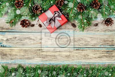 Christmas tła z pudełko, jodła oddział i szyszka na drewnianym pokładzie tamtejsze, świąteczny efekt śniegu, Boże Narodzenie ramki, widok z góry z miejsca na kopię
