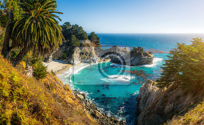 Fototapeta Classic postcard view of famous McWay Falls in scenic golden evening light at sunset on a beautiful sunny day with blue sky in summer, Julia Pfeiffer Burns State Park, Big Sur, California, USA
