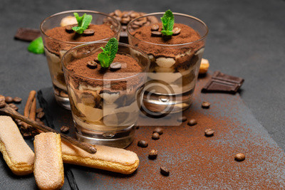 Fototapeta Classic tiramisu dessert in a glass and savoiardi cookies on dark concrete background