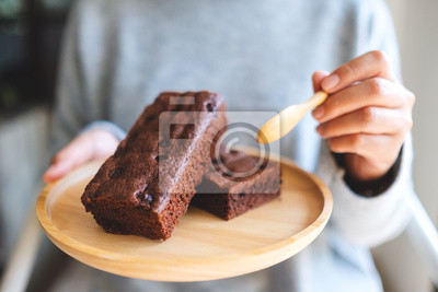 Fototapeta Closeup image of a woman eating delicious brownie cake with spoon