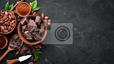 Fototapeta Cocoa beans, chocolate, cocoa butter and cocoa powder on a black background. Top view. Free copy space.