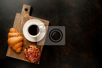 Fototapeta Coffee and croissant, bun on a stone table. morning breakfast, with copy space for text