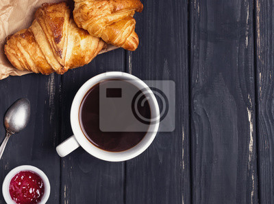 Fototapeta Coffee with croissants on the black wooden table, top view.