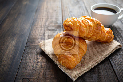 Fototapeta croissants and coffee on old wooden table.