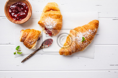 Fototapeta Croissants with berry jam on white wooden background.