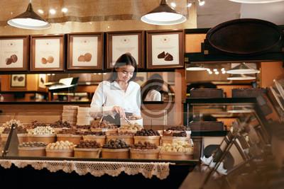 Fototapeta Cukiernia. Kobieta sprzedaży cukierki czekoladowe w sklepie
