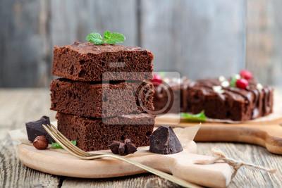 Fototapeta Czekoladowy punktu tort, deser z dokrętkami na drewnianym tle.