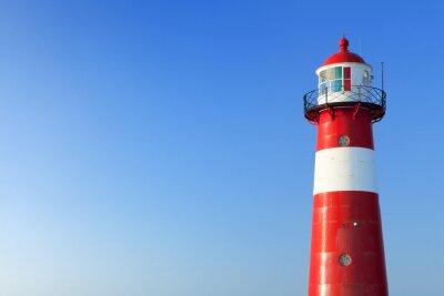 Fototapeta Czerwona i biała latarnia morska i jasnego nieba