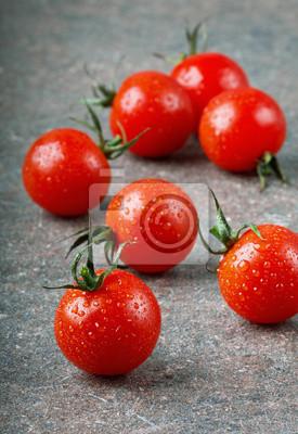 Czerwone pomidory czereśniowe w kropli wody na ciemnej powierzchni