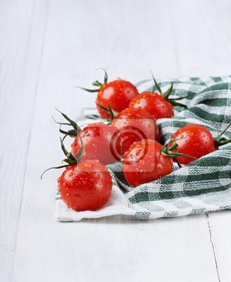 Czerwone pomidory czereśniowe w kropli wody na zielonym serwetki lniane