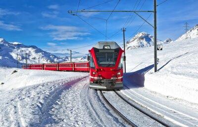 Fototapeta Czerwony szwajcarski pociągu przez śnieg