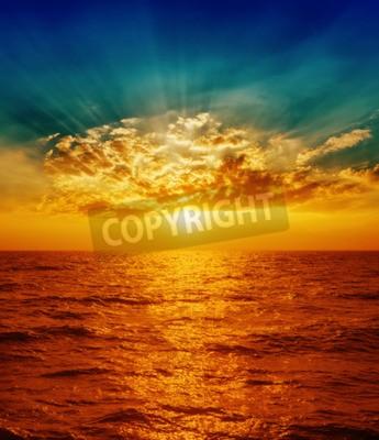 Fototapeta czerwony zachód słońca nad morzem w chmurach