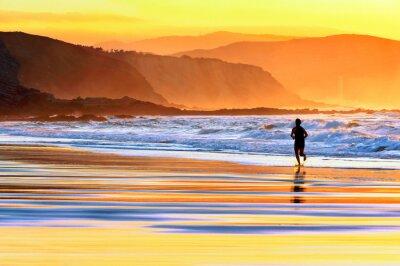 Fototapeta człowiek działa na plaży o zachodzie słońca