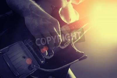 Fototapeta Człowiek gra na gitarze elektrycznej w kolorze czarnym i żółtym