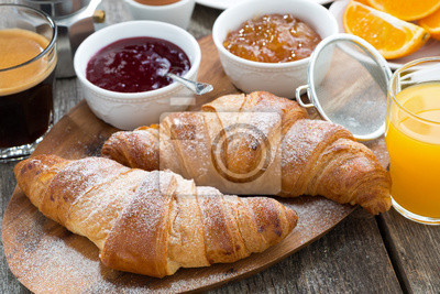 Fototapeta delicious breakfast with fresh croissants on wooden table